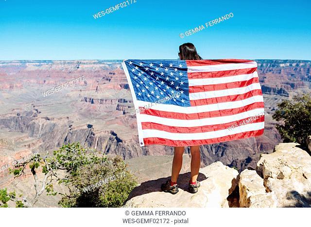 USA, Arizona, back view of woman with American flag enjoying view of Grand Canyon National Park