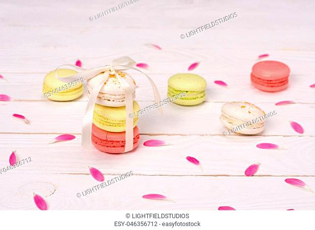 Still life of fresh macarons on the table with pink petals. sweets background concept