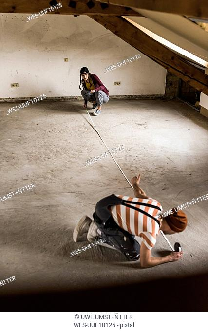 Young man and woman measuring floor on construction site