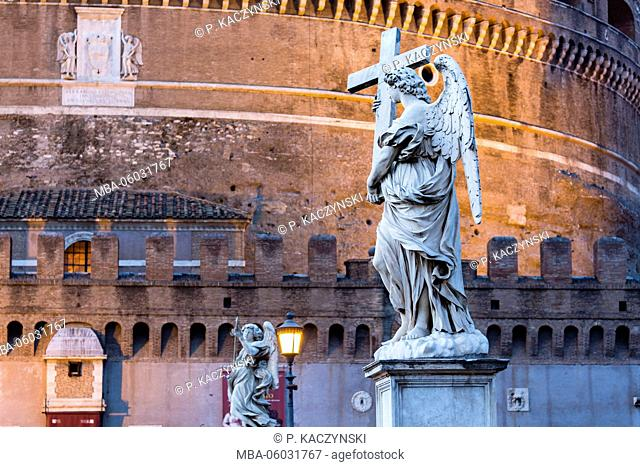 Statue on the Ponte Sant'Angelo by an illuminated street lantern, dusk