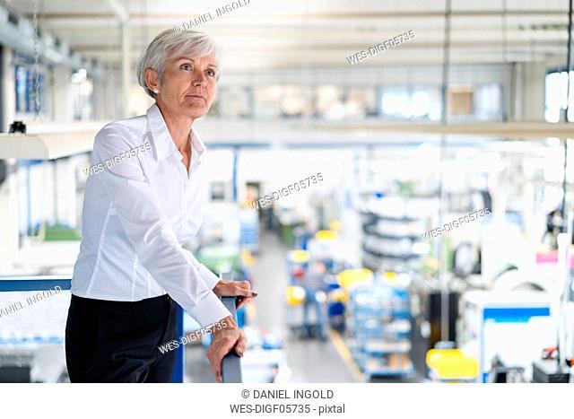 Senior businesswoman on upper floor in factory overlooking shop floor
