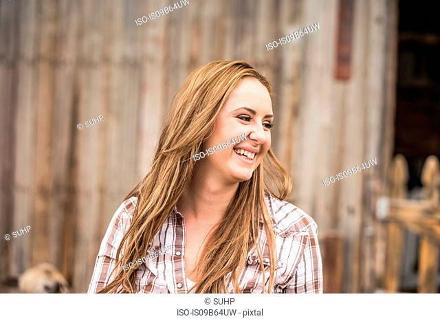Young woman outdoors, on farm, smiling