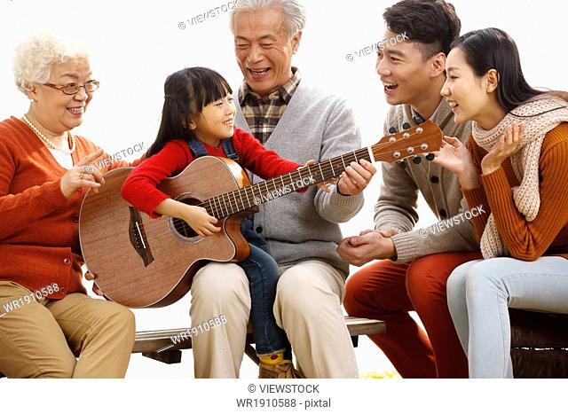 Happy family outdoor play the guitar