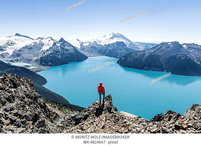 View from Panorama Ridge Hiking Trail, Hiker on a Rock, Garibaldi Lake, Guard Mountain and Deception Peak, Back Glacier, Garibaldi Provincial Park