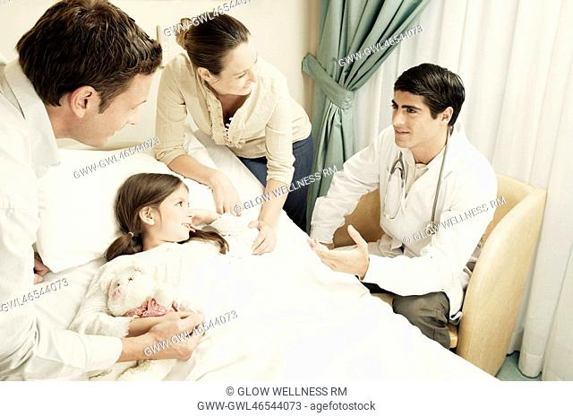 Girl on a hospital bed and her parents discussing with a doctor