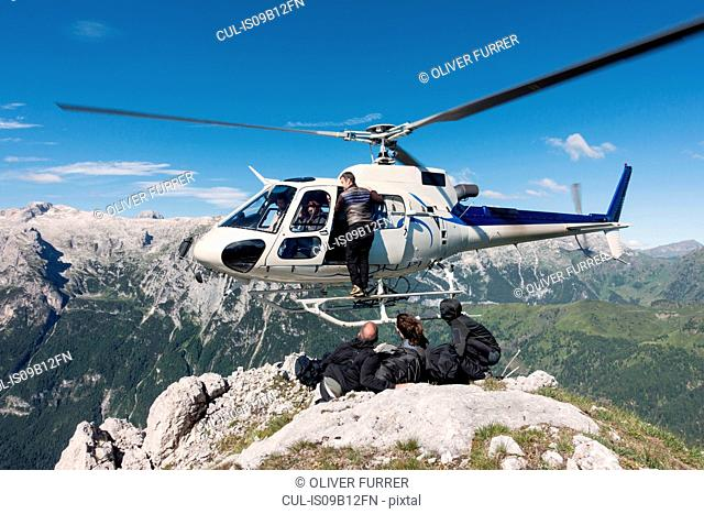 Male and female BASE jumping team exiting helicopter on top of mountain at Col di Pra, Italian Alps, Alleghe, Belluno, Italy