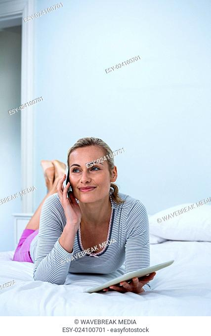 Smiling woman holding digital tablet while talking on phone on bed