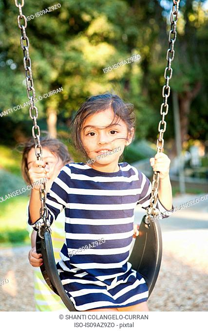 Young girl swinging on playground swing