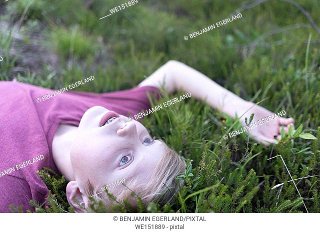lonely thoughtful teen boy laying in grass, dreaming at day