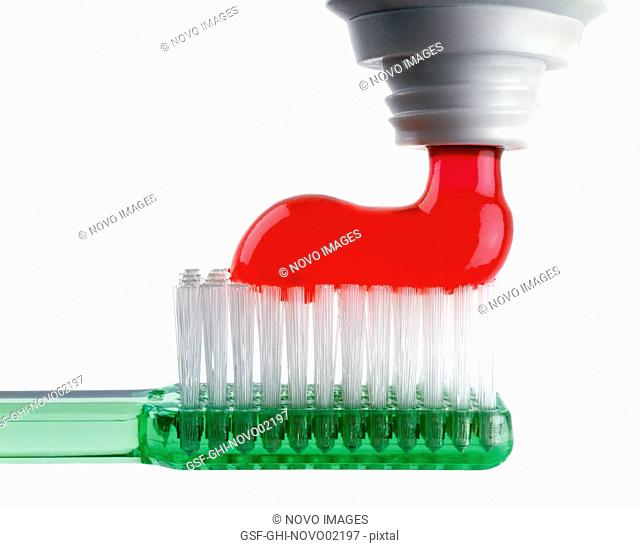 Red Toothpaste Being Squeezed out onto Green Translucent Toothbrush on White Background