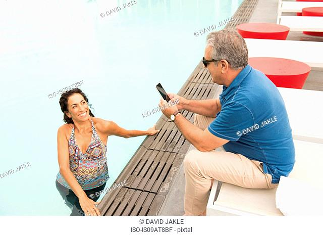 Senior man photographing wife with smartphone from poolside
