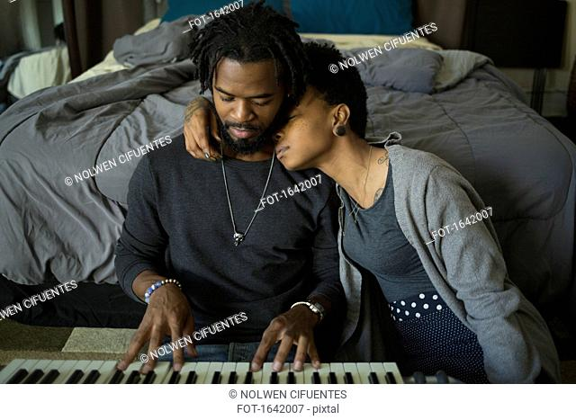 Woman leaning on man playing piano at home