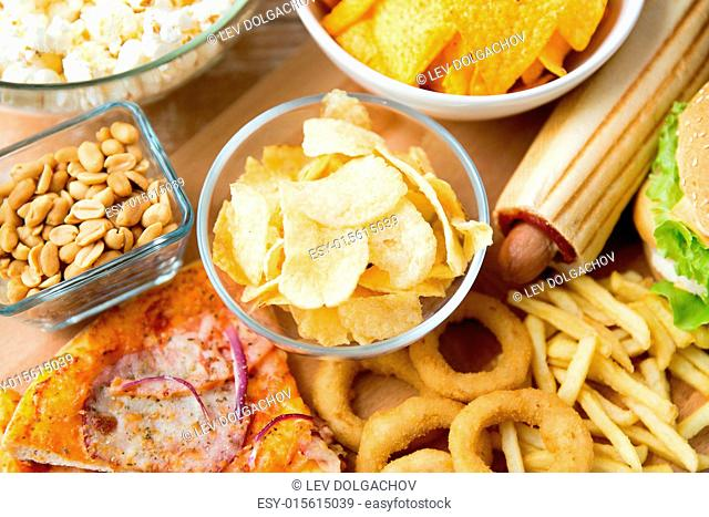 fast food and unhealthy eating concept - close up of different fast food snacks on wooden table