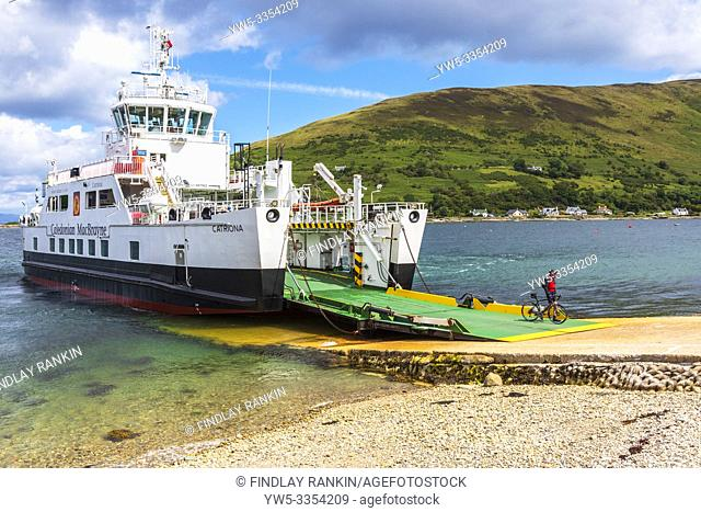 Cyclist disembarking from the Caledonian MacBrayne ferry at the slipway near Lochranza, Isle of Arran, near Newton Point on the Firth of Clyde, Arran, Scotland