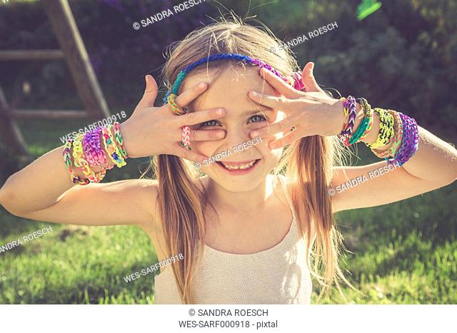 Portrait of smiling ittle girl showing her loom bracelets