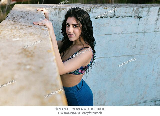 Smiling young brunette woman with bikini in an old empty pool