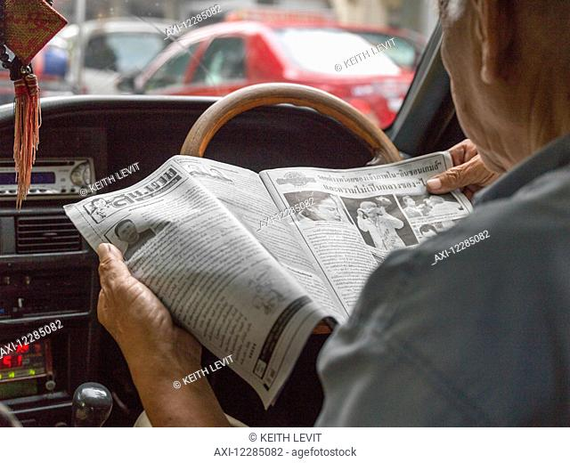 Man reading a newspaper in the drivers seat of a car; Bangkok, Thailand