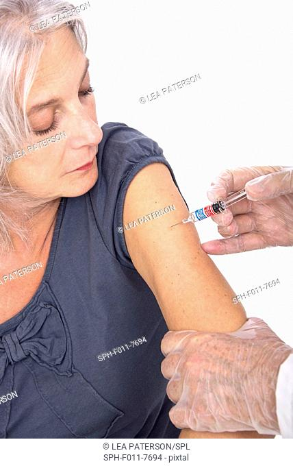 MODEL RELEASED. Mature woman receiving a vaccination