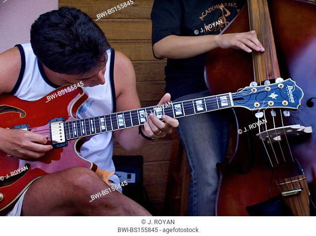 electric guitar player with a bass player in the background, Brazil