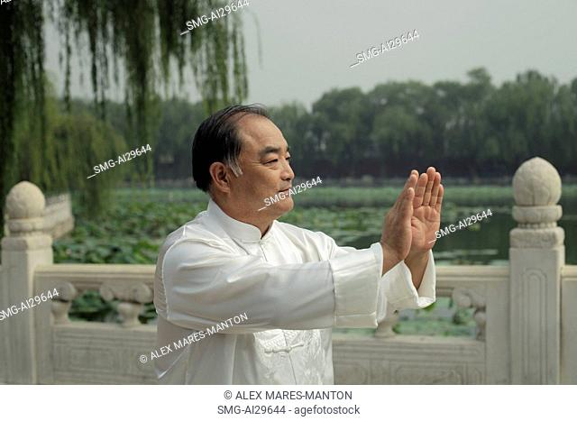 Older man doing Tai Chi in a park, Beijing, China