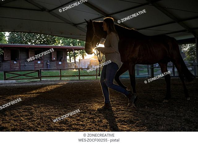 Smiling young woman with horse in riding arena