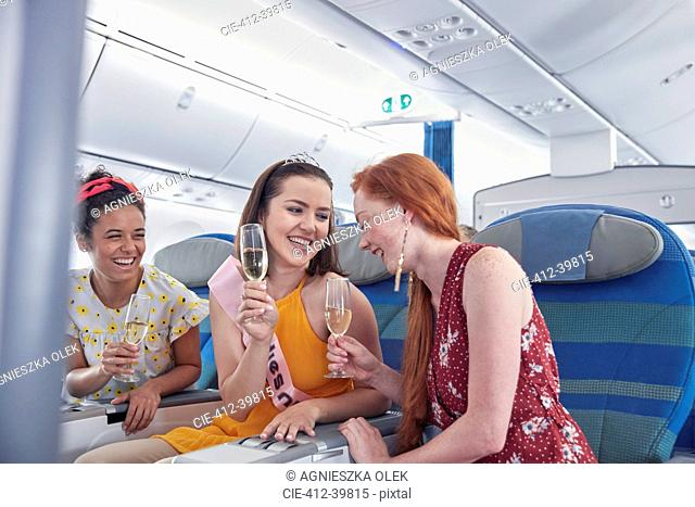 Young women friends laughing, drinking champagne in first class on airplane