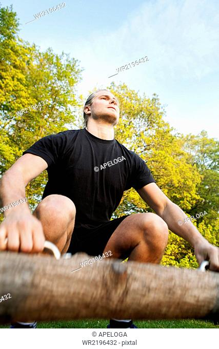 Low angle view of young man exercising with log at park