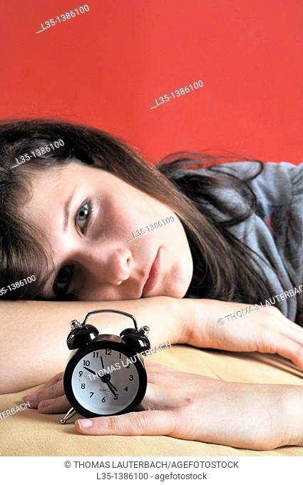 Young woman with an old alarm clock early in the morning