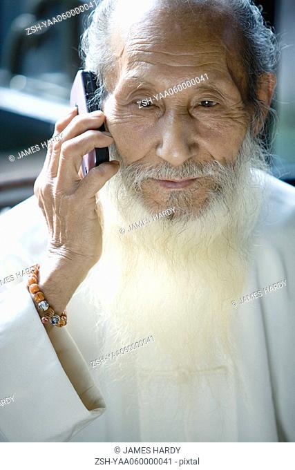 Elderly man in traditional Chinese clothing with long beard, using cell phone