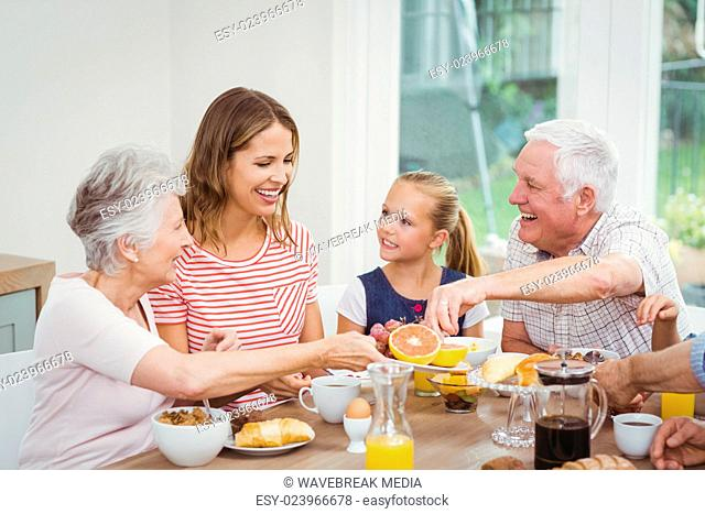 Multi-generation family eating fruits during breakfast