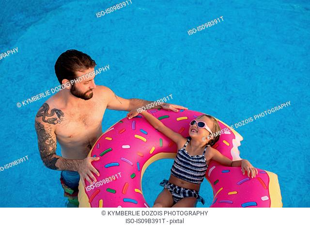 Young girl in swimming pool, relaxing on inflatable ring, father standing beside her