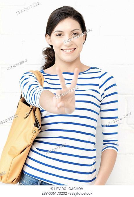 education concept - lovely teenage girl showing v-sign