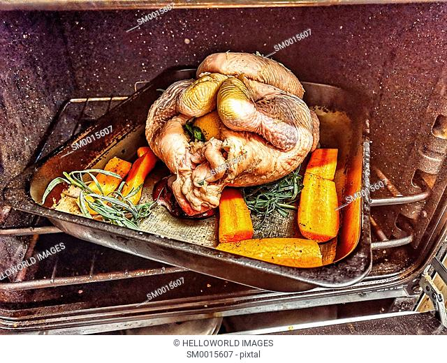 Whole raw chicken stuffed with lemon and herbs and with carrots in roasting tin in the oven