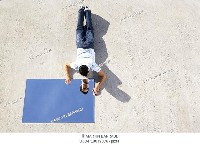 Man lying down on ground with mirror and reflection