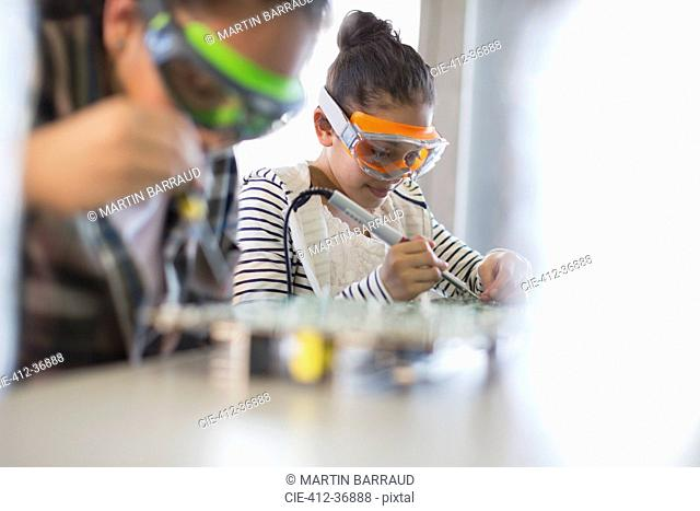 Focused girl students soldering circuit boards in classroom