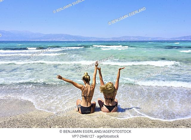 best friends, two vibrant girls sitting in bikini on beach and enjoying sea water. Dutch ethnicity. At holiday destination Chrissi Island, Crete, Greece