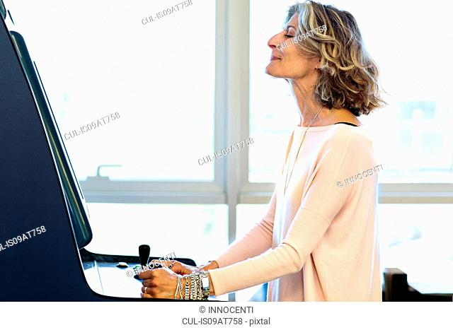 Senior female designer playing on games machine in office