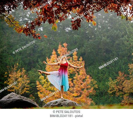 Caucasian ballerina dancing on rock in park