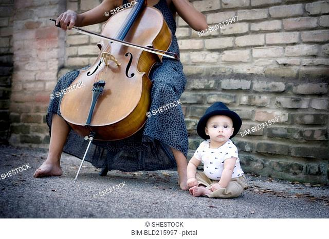 Mixed race musician playing cello with baby daughter