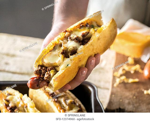 A hand holding a Texas chilli dog