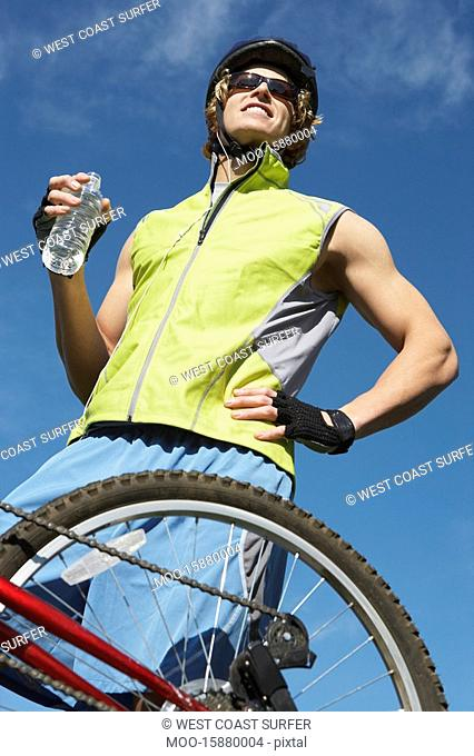 Male cyclist holding water bottle outdoors