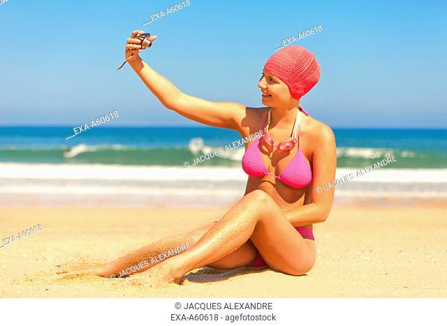 Young woman in bikini taking photograph of herself on beach