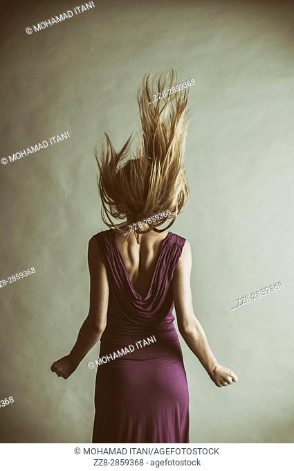 Rear view of a young blond woman wearing a purple dress flicking her hair up