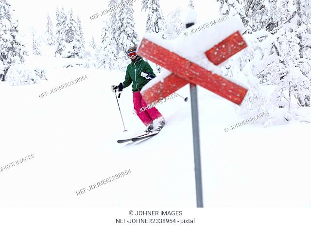 Person skiing, trail markings on background