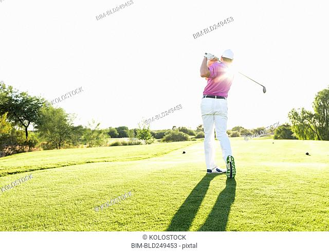 Hispanic golfer teeing off on golf course
