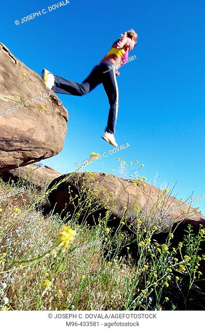 Female jumping rocks during trail run. Rocky Peak. California. USA