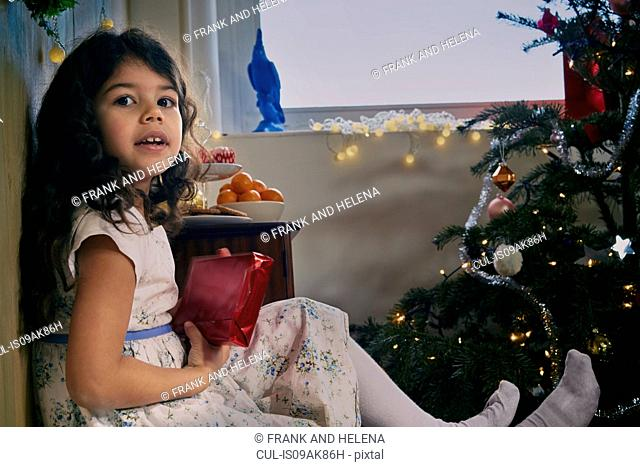 Portrait of girl sitting on floor with christmas present