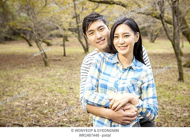 Portrait of young smiling couple hugging staring at front against forest