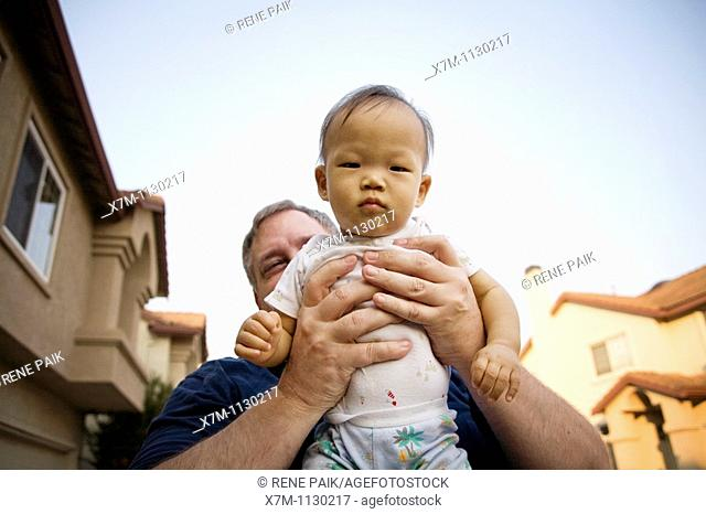 A tiny Korean baby boy being held in a Caucasian man's giant hands