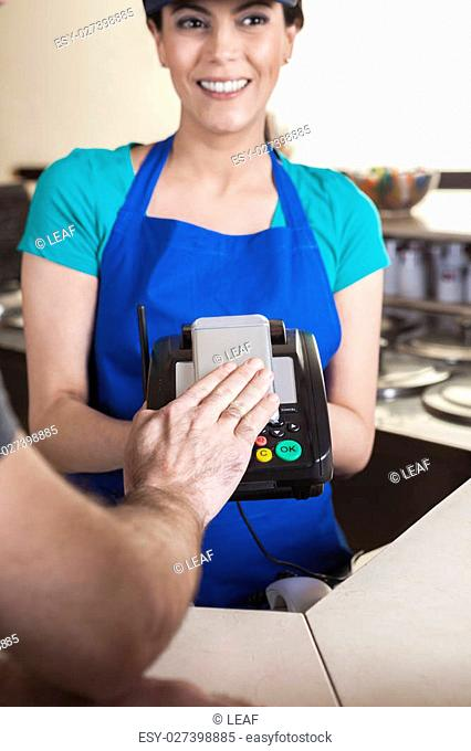 Cropped image of customer's hand making NFC payment on mobile phone while waitress smiling in ice cream shop